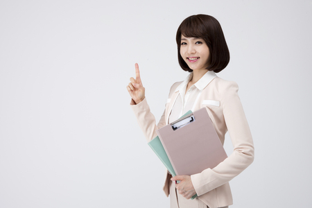 Portrait of Asian business woman pointing something with file isolated on white Stock Photo