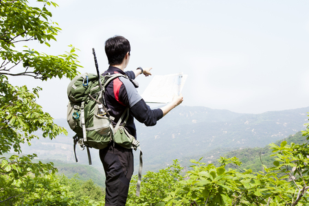 Portrait of Asian man pointing somewhere with map on top mountain outdoors