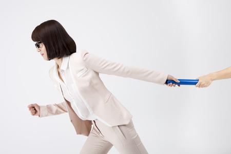Portret van Aziatische bedrijfsvrouw die de knuppel overgaat die op wit wordt geïsoleerd Stockfoto