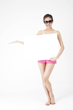 Asian woman in sunglasses holding white board on summer day isolated on white