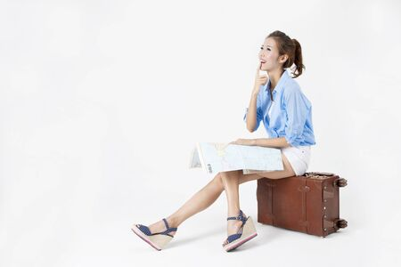 Asian woman checking map sitting on suitcase on summer day isolated on white
