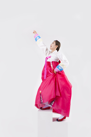 Asian woman in Korean traditional clothes grabbing something on upper isolated on white Stok Fotoğraf