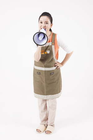 loudspeaker: Asian housewife in apron shouting with loudspeaker isolated on white