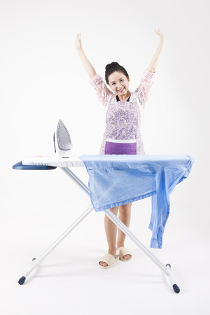 Asian housewife in apron done the ironing isolated on white Stock Photo - 87007288