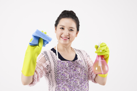 Asian housewife in apron cleaning with spray isolated on white