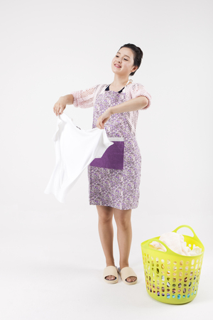 Asian housewife in apron hanging out the wash isolated on white Reklamní fotografie