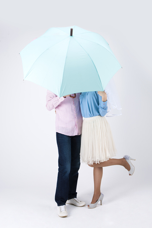 Asian happy couple with umbrella isolated on white 免版税图像