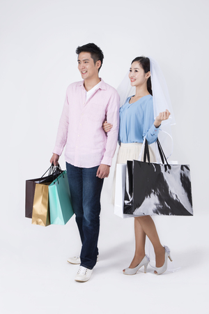 Asian happy couple with shopping bags isolated on white