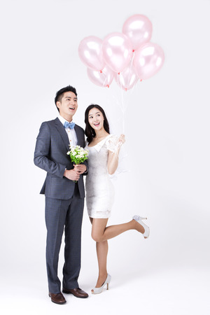 Asian new married couple with balloons isolated on white 免版税图像