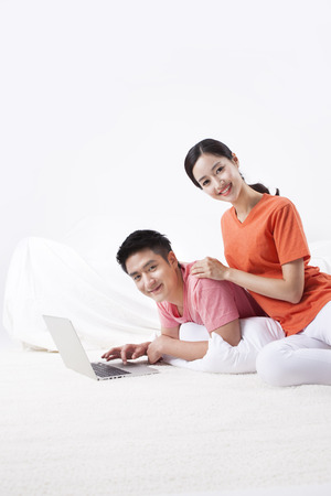 Asian happy couple using laptop isolated on white 免版税图像