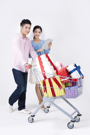 Asian happy couple with tablet pc and shopping cart isolated on white