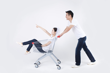 Asian happy man carrying lover in shopping cart isolated on white