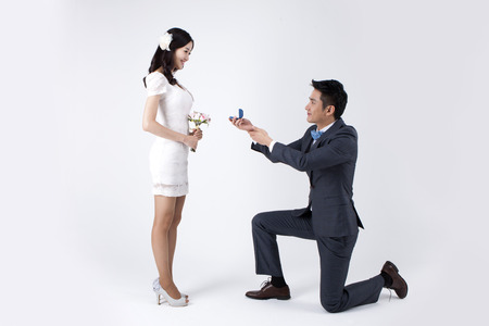Asian new married man giving ring while kneeling down isolated on white