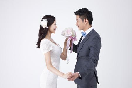 Aziatisch gelukkig paar met boeket dat op wit wordt geïsoleerd Stockfoto