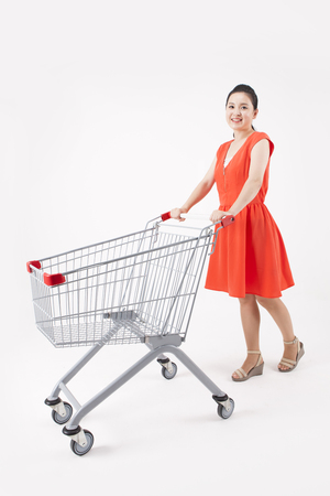 Asian beautiful woman with shopping cart isolated on white Stock Photo