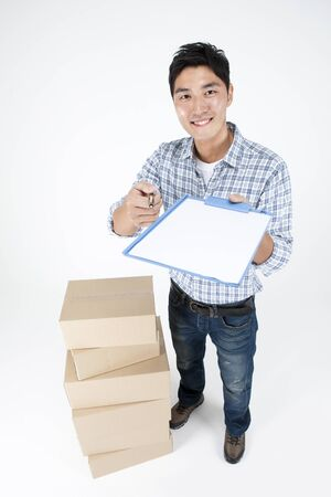 Asian handsome man giving document with boxes isolated on white