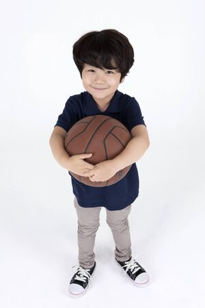 Asian cute boy with basketball isolated on white