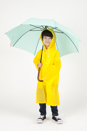 Asian cute boy in raincoat with umbrella isolated on white Stock Photo