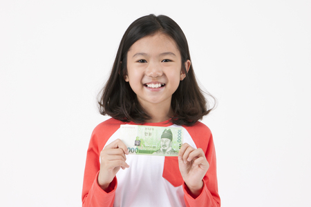 Asian female child pointing with money isolated on white Stock Photo