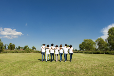Happy Asian people group putting arms around each others shoulders on grass