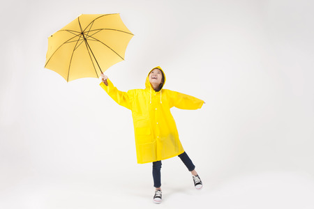 Asian female child in raincoat with umbrella isolated on white