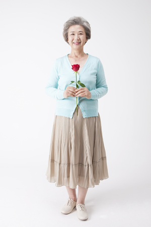 Asian old aged woman with rose isolated on white Stock Photo