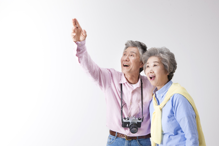Asian old aged couple with camera isolated on white