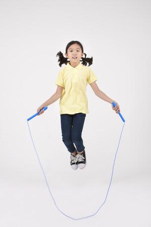 Asiatisches weibliches Kind, welches das Sprungseil lokalisiert auf Weiß überspringt
