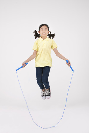Asian female child skipping jump rope isolated on white
