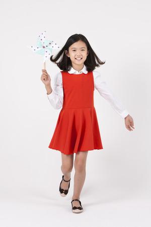 Asian female child with pinwheel isolated on white Stock Photo