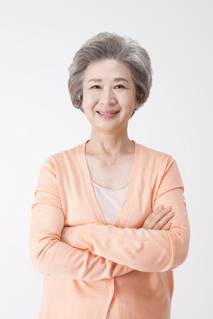 Aziatische oude oude vrouw met glimlach die op wit wordt geïsoleerd
