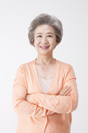 Donna invecchiata anziana asiatica con il sorriso isolato su bianco