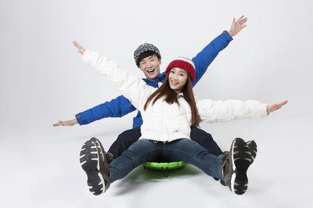Asian happy couple enjoying sledding isolated on white Stock Photo