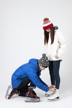 Asian happy couple tying skating shoes isolated on white