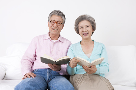 Asian old aged couple reading book on sofa bed isolated on white
