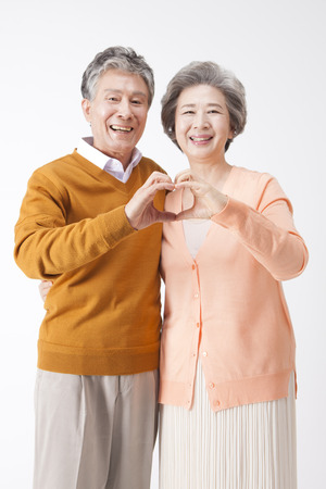 Asian old aged couple making heart shape with fingers isolated on white Imagens