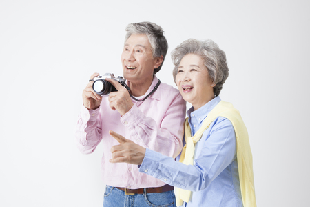 Asian old aged couple taking a picture isolated on white