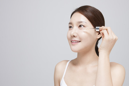 Asian young woman applying serum isolated on white