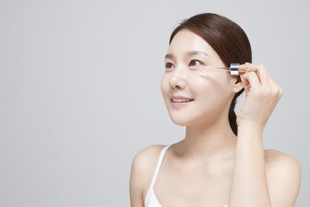 아시아 젊은 여자가 흰색으로 격리 혈청을 적용