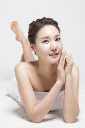 lug: Asian young woman lying on lug isolated on white