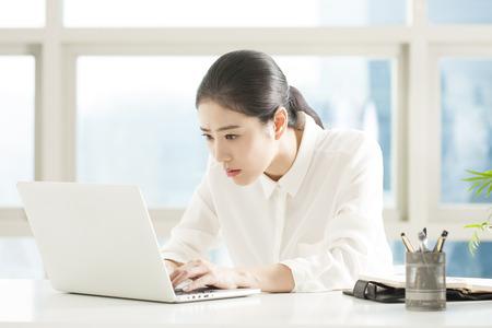 Asiatische berufstätige Frau, die Laptop auf dem Schreibtisch im Büro verwendet