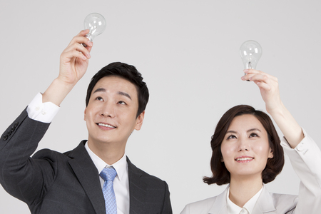 Asian business couple with light bulb isolated on white Stock Photo
