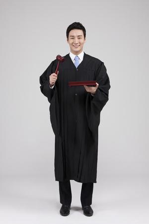 白で隔離の小槌を持ってアジア裁判官 写真素材