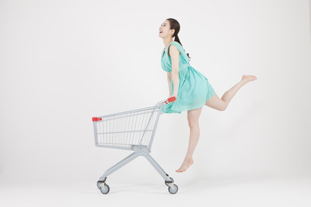 Aziatische jonge vrouw springen met boodschappenwagentje geïsoleerd op wit