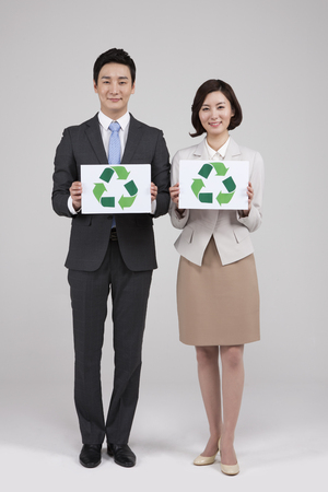 Asian business couple with recycling board isolated on white Stock Photo