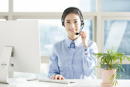 Asian female telemarketer working with laptop in office