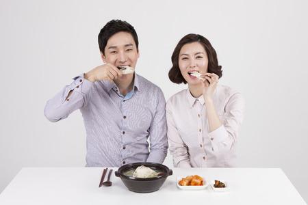 Asian business couple eating samgyetang isolated on white