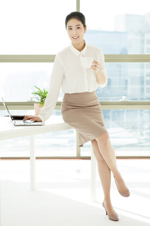 Asian business woman drinking coffee in office