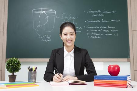 Aziatische vrouwelijke leraarszitting op het bureau op bordachtergrond Stockfoto