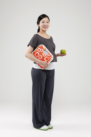 Asian pregnant woman with apple and scale isolated on white